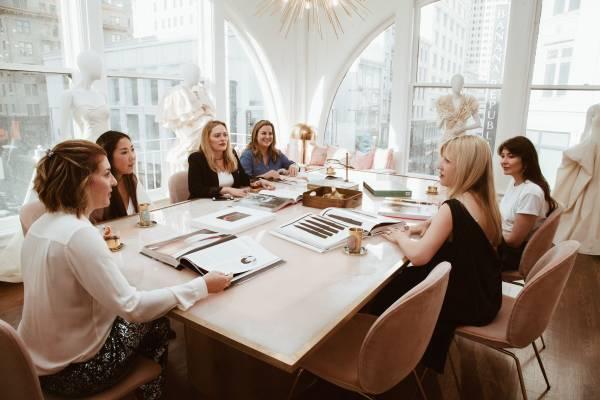 TEG Team Sat around Table Discussing Ideas