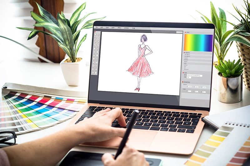 Designer working on laptop to create fashion design sketches