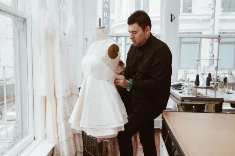 Designer putting a dress on a mannequin