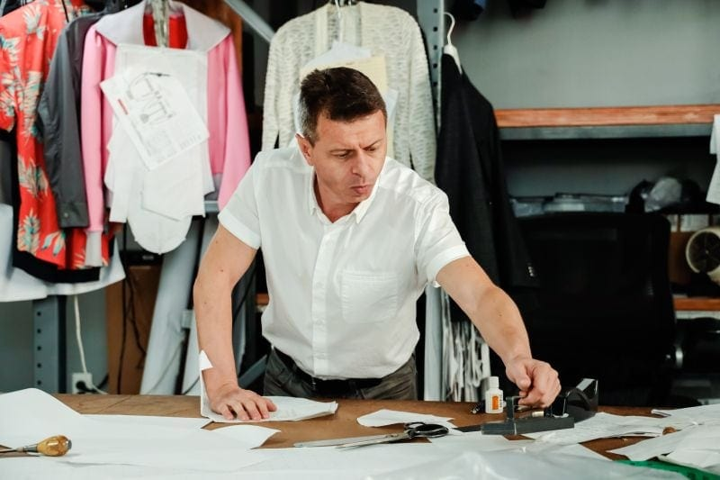 pattern making: Man adding a marker to a piece of fabric