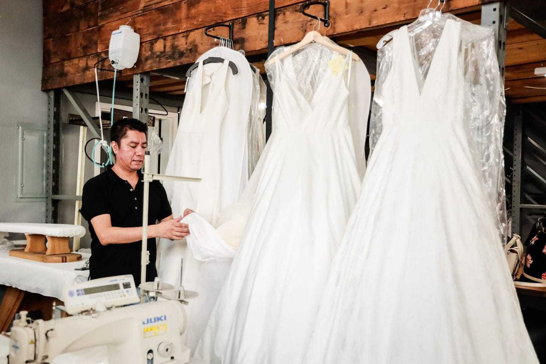 fashion line sheet: Designer examining wedding gowns inside a manufacturing studio