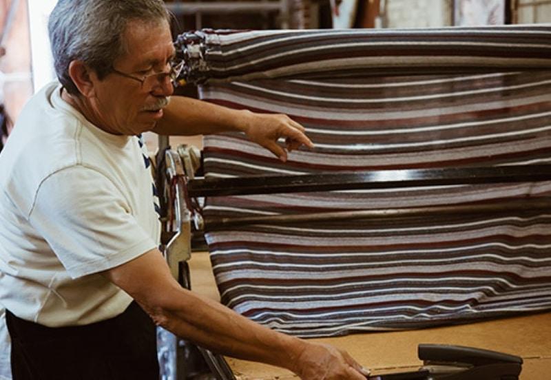 fabric sourcing: Elderly man cutting fabric