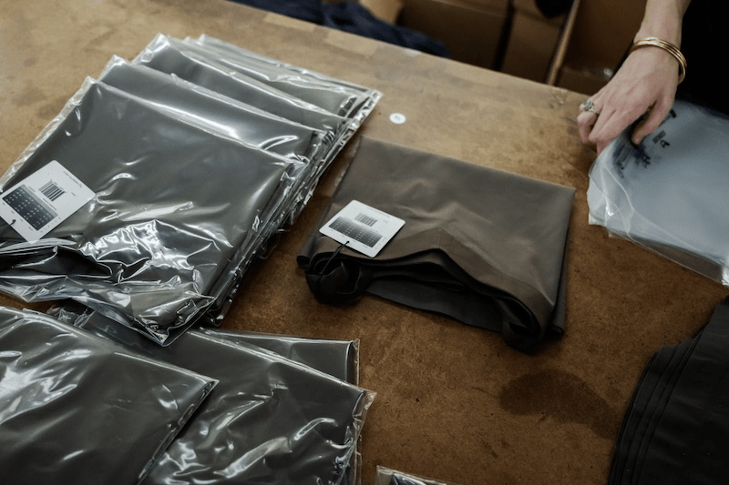 small batch manufacturers: Packed clothes on top of a wooden surface
