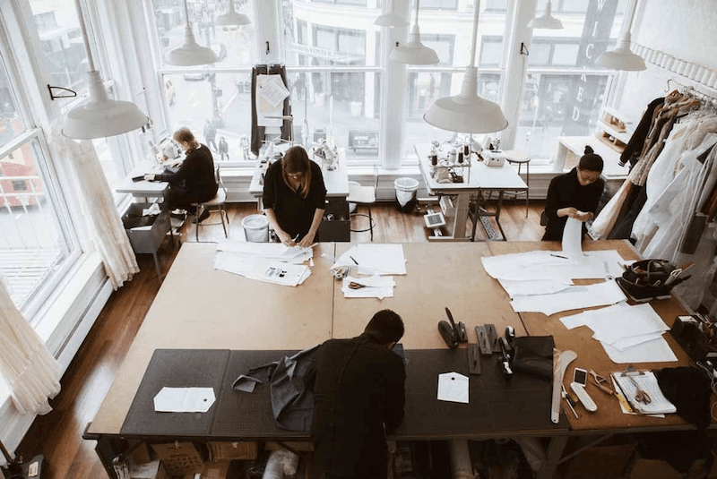 Group of people working in a small fashion production studio