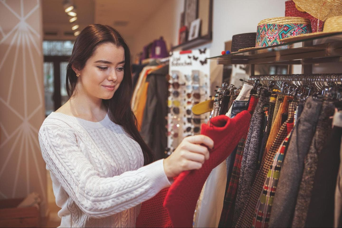 fashion merchandising: Smiling woman examining a sweater at a store
