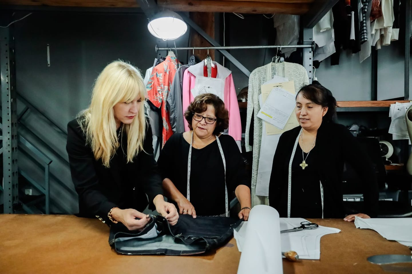 Jennifer Evans and two clothing manufacturers examining fabric and starting a clothing line
