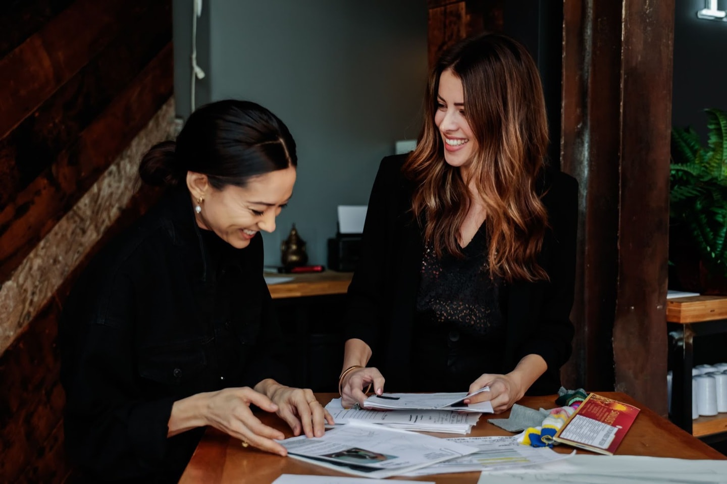 Two clothing manufacturers laughing while designing a clothing line