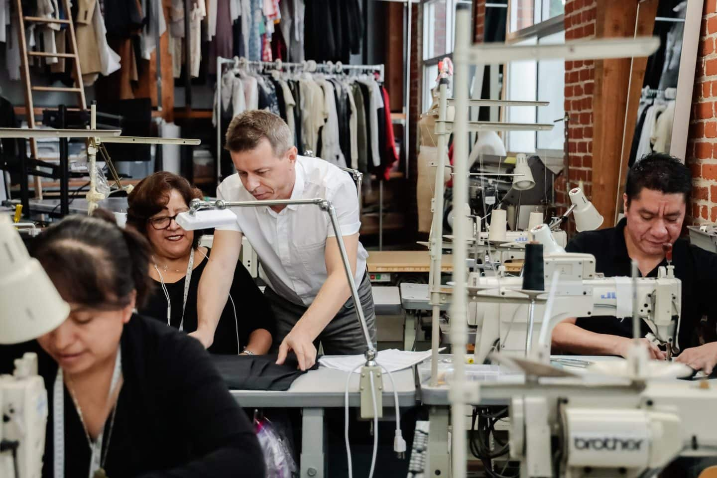 L.A. Clothing manufacturer going over pattern making with seamstresses