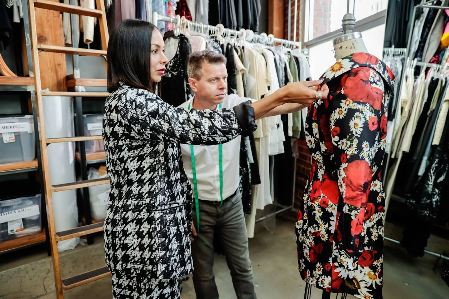 Two clothing manufacturers examine a dress on a mannequin