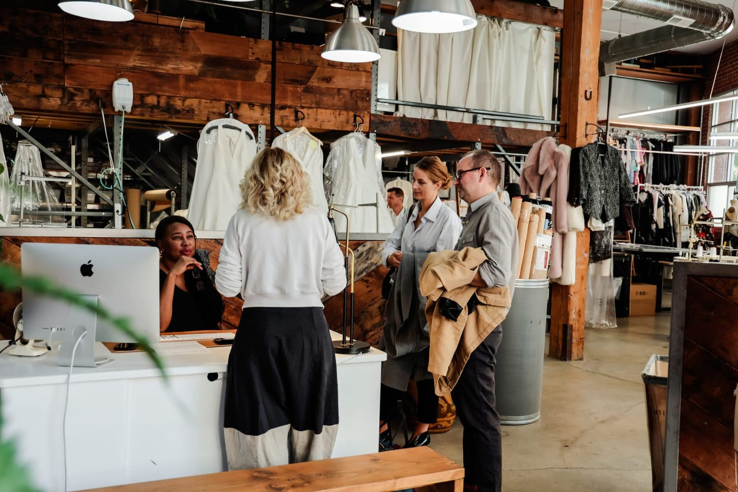Four clothing manufacturers gathered around a desk discussing fashion