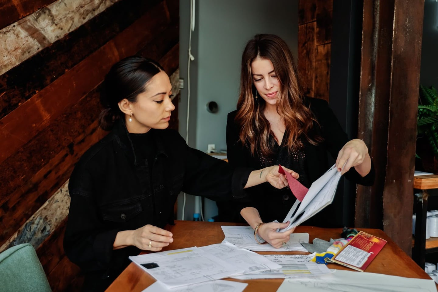Two fashion designers going over their clothing line fabrics