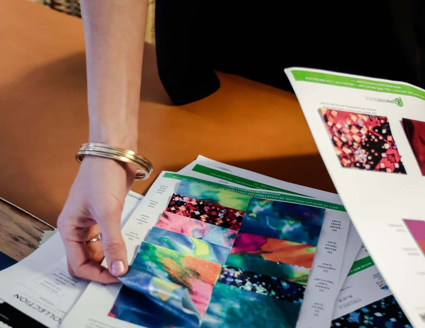 closeup of a fashion designer examining fabric swatches for a clothing line