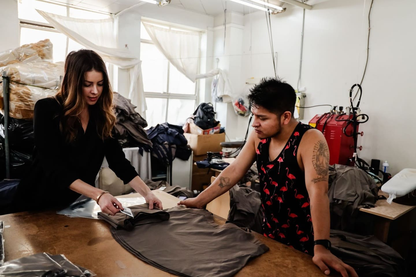 Two clothing manufacturers examinigin fabric and starting a clothing line