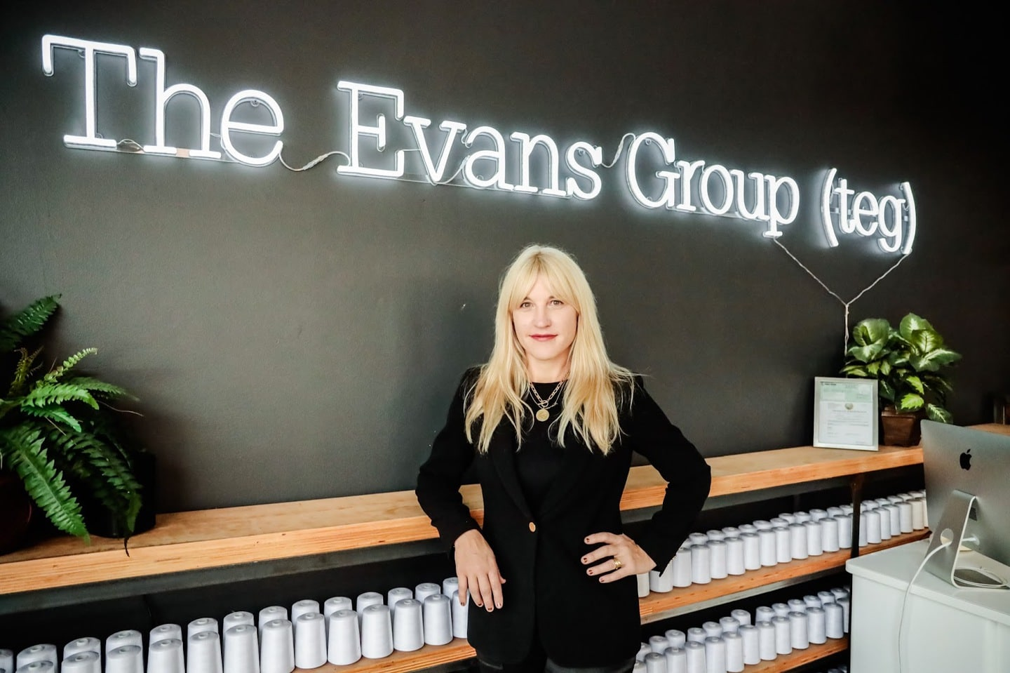Jennifer Evans standing in front of neon TEG sign in Los Angeles