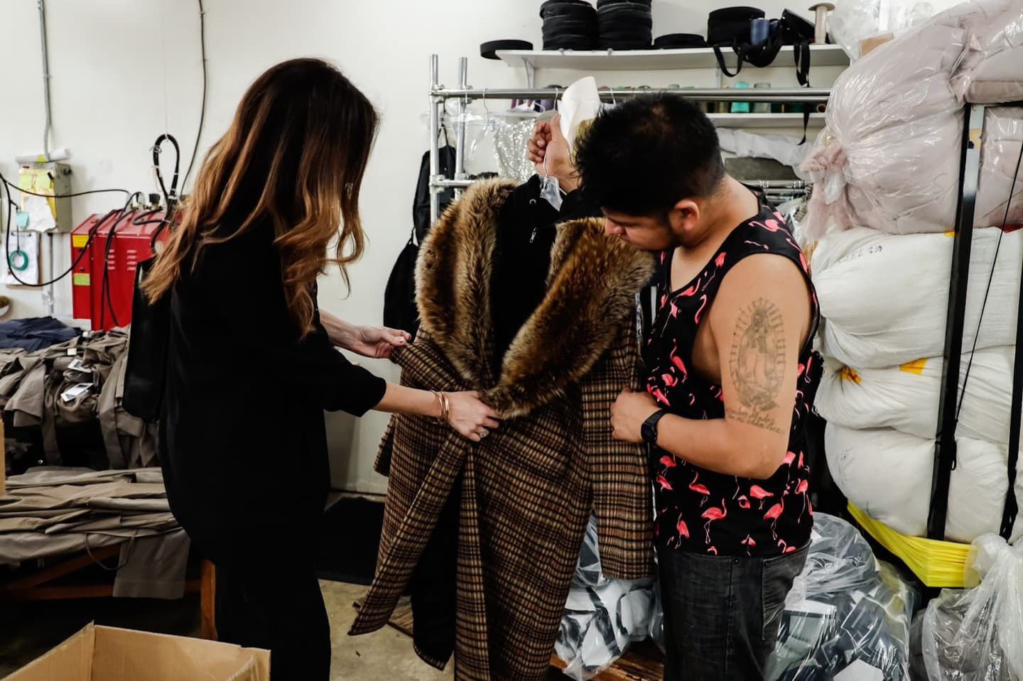 Two clothing designers examining sustainable fashion materials and fabric