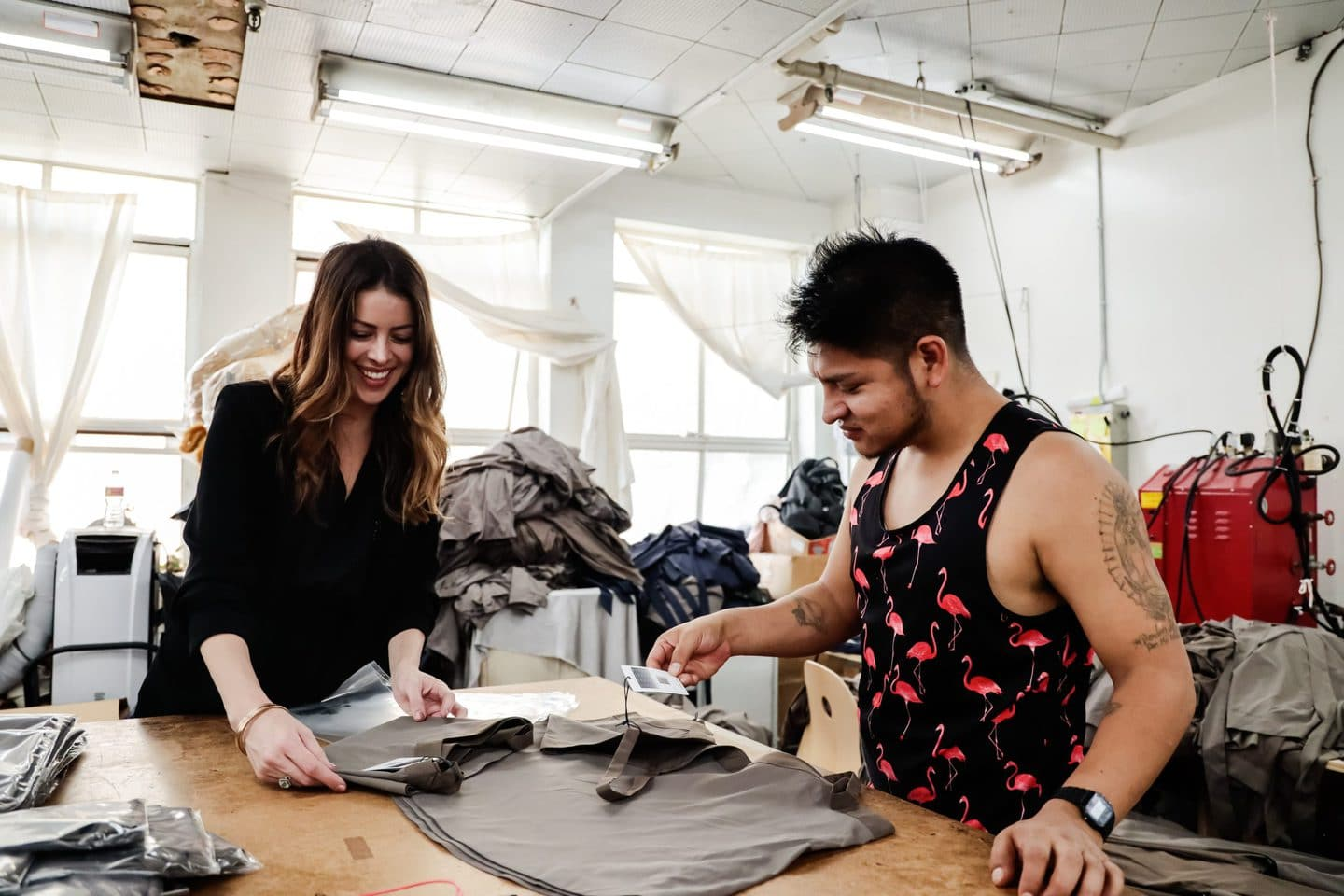 Two Los Angeles Clothing manufacturers going over the natural fibers in a new design