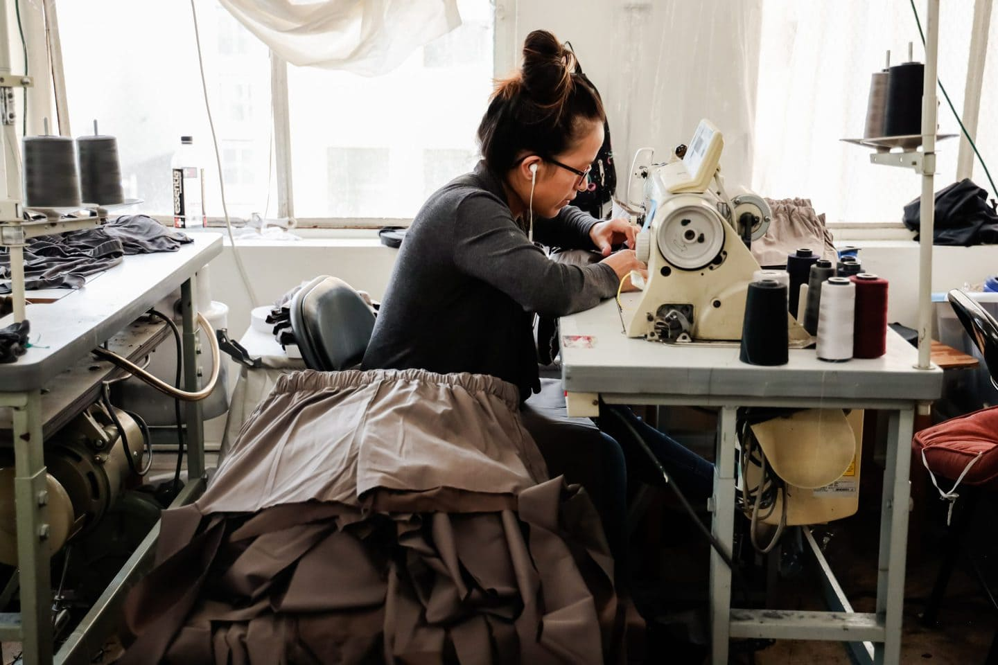 A Los Angeles clothing manufacturer working on bespoke fashion on a sewing machine