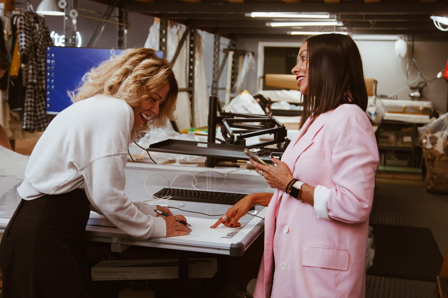 Two Los Angeles fashion designers laughing while consulting a fashion mood board