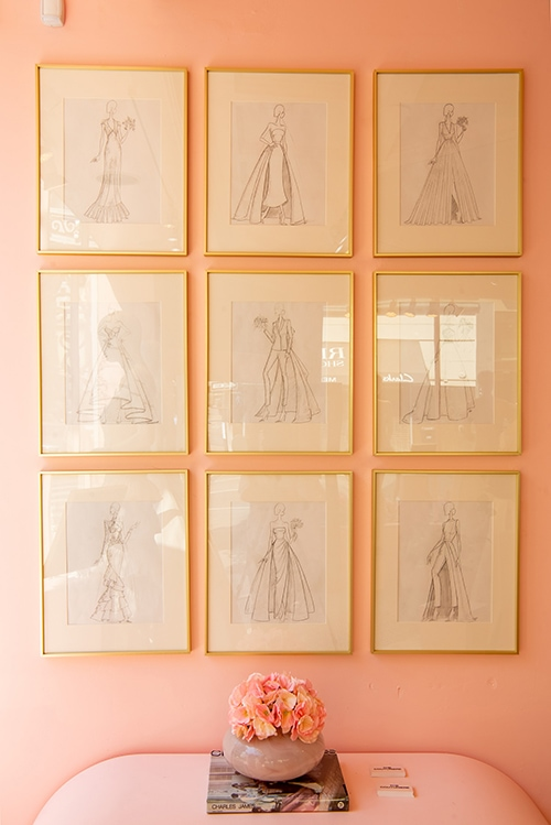nine fashion sketeches hanging up on a pink wall