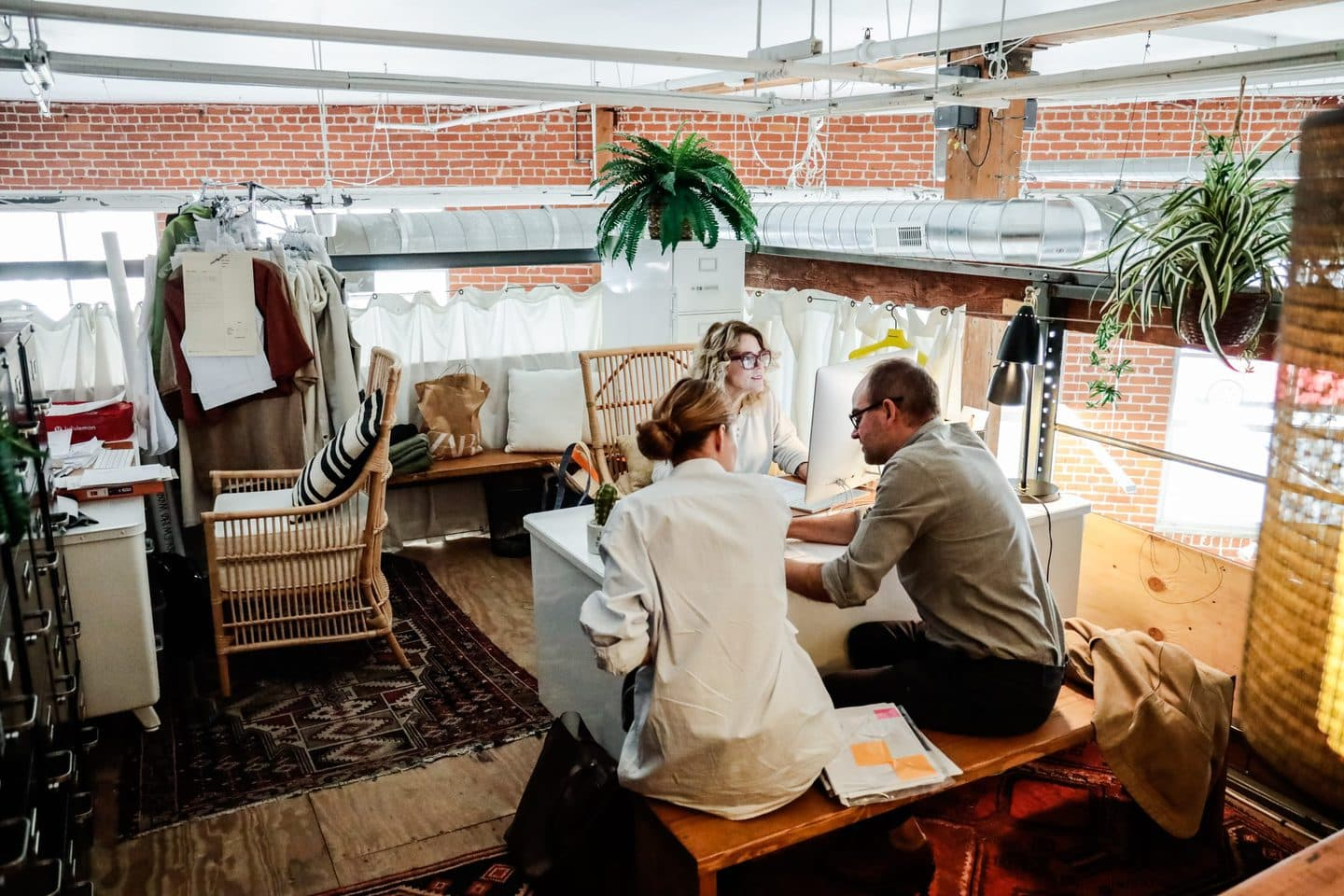 Three Los Angeles clothing manufacturers consulting a design in an office setting