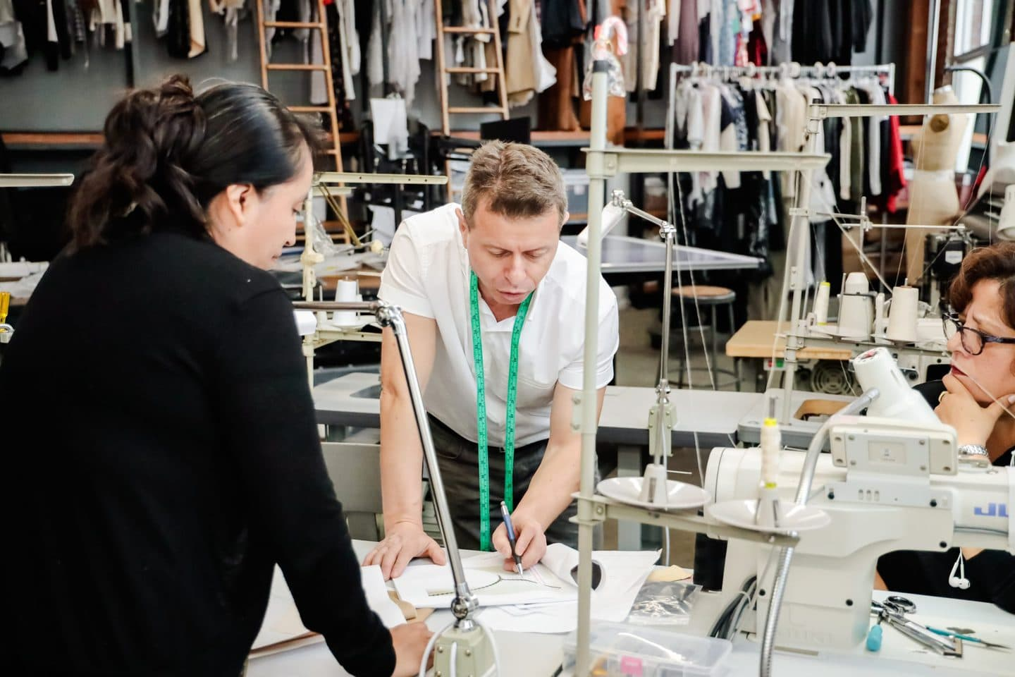Two Los Angeles pattern makers going over a design in a clothing manufacturing studio
