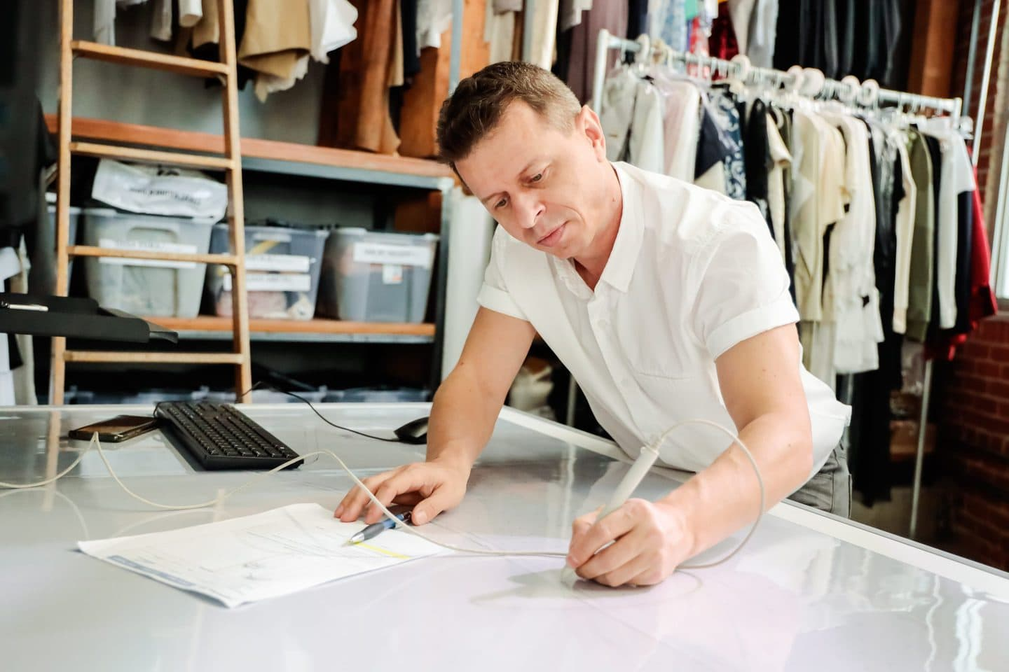 Los Angeles pattern maker working on a fashion sketch at a white desk