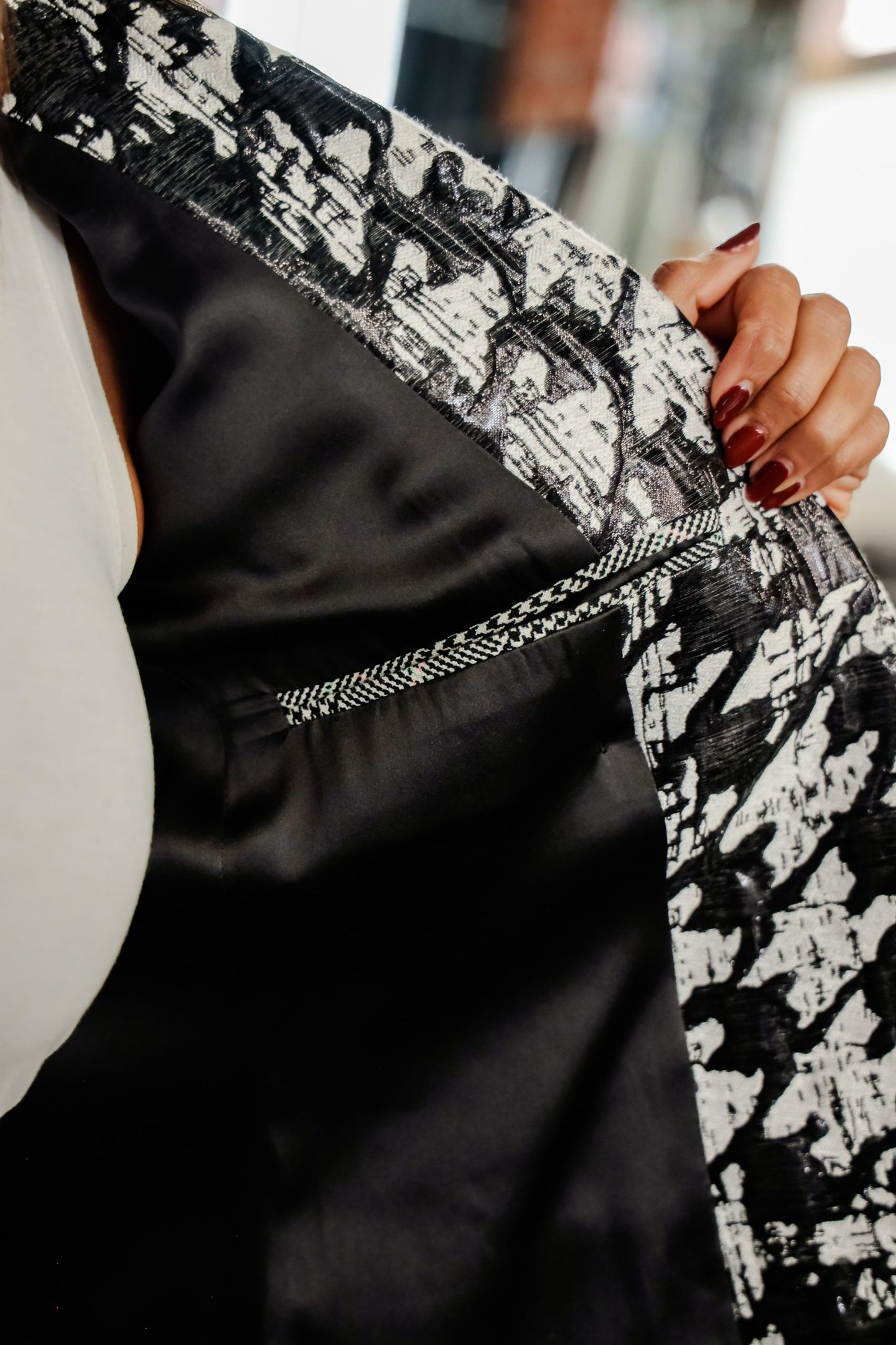 Fashion model exposing the inside lining of a houndstooth jacket created by a pattern maker