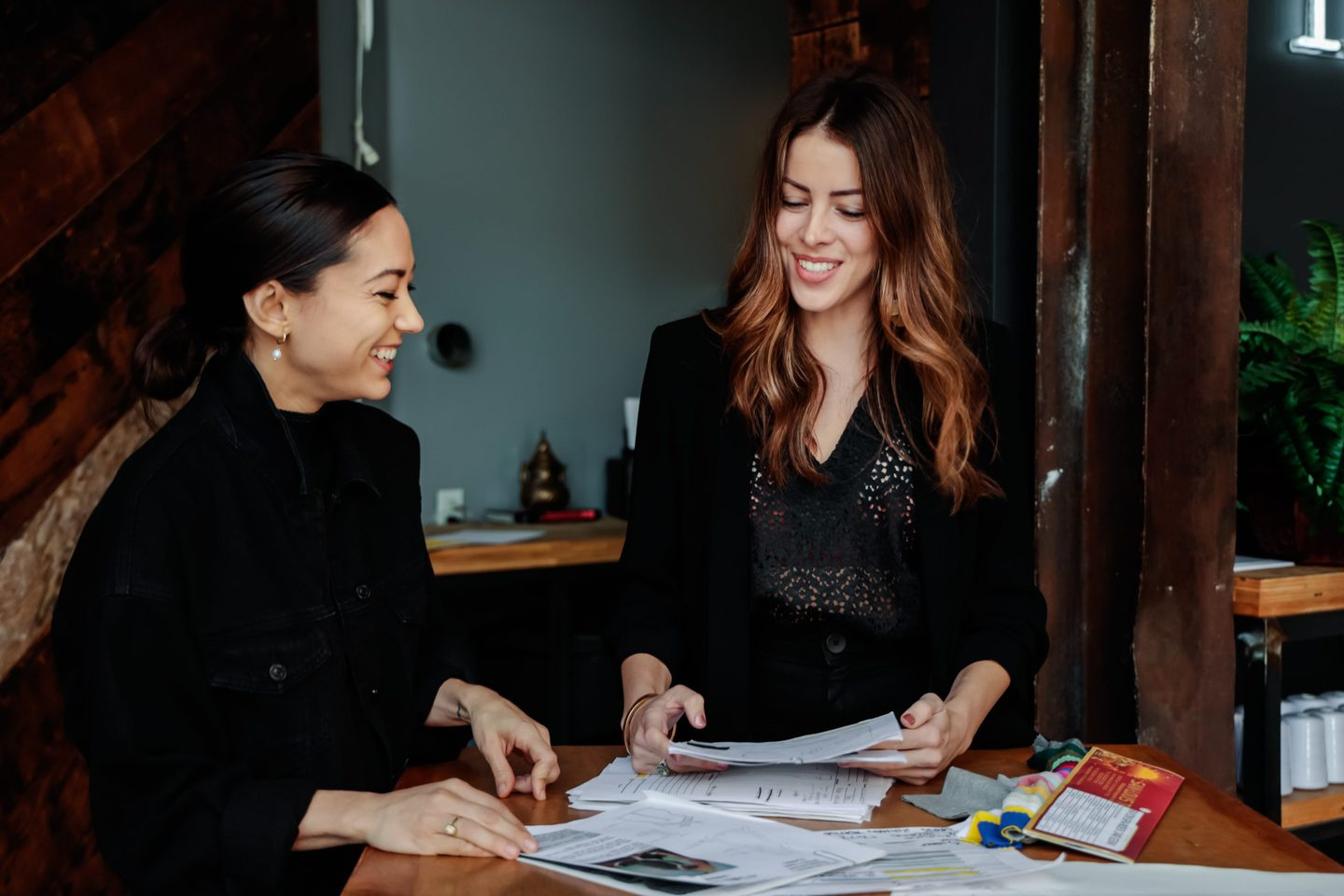 Two fashion designers smiling with one another after finding a clothing manufacturer in Los Angeles