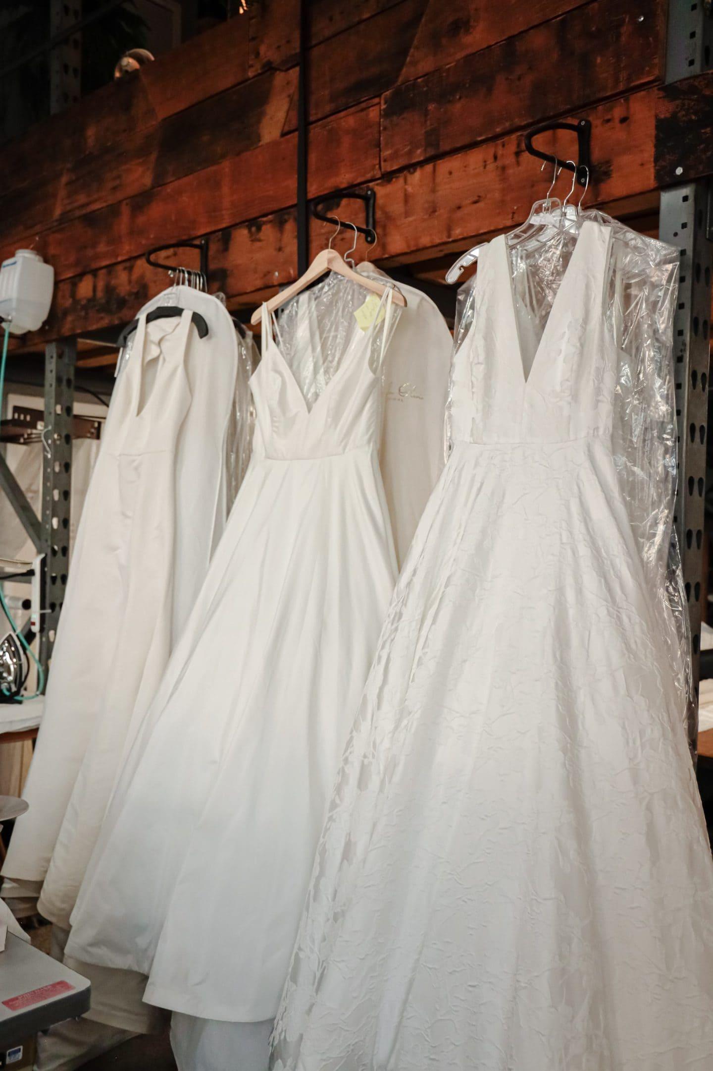 Three wedding dresses hanging on racks at a clothing manufacturer